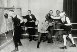 Two blindfolded boxers and a referee in a boxing ring, c. 1925